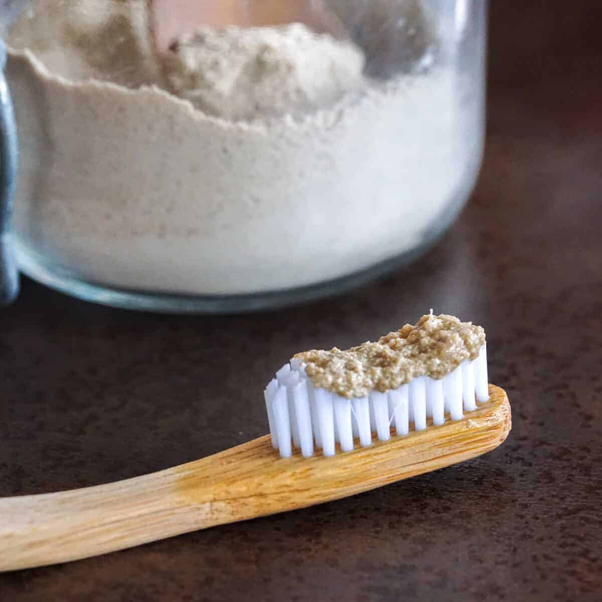 Closeup of tooth powder on a bamboo toothbrush. In the background theres a glass jar filled with the homemade tooth powder.