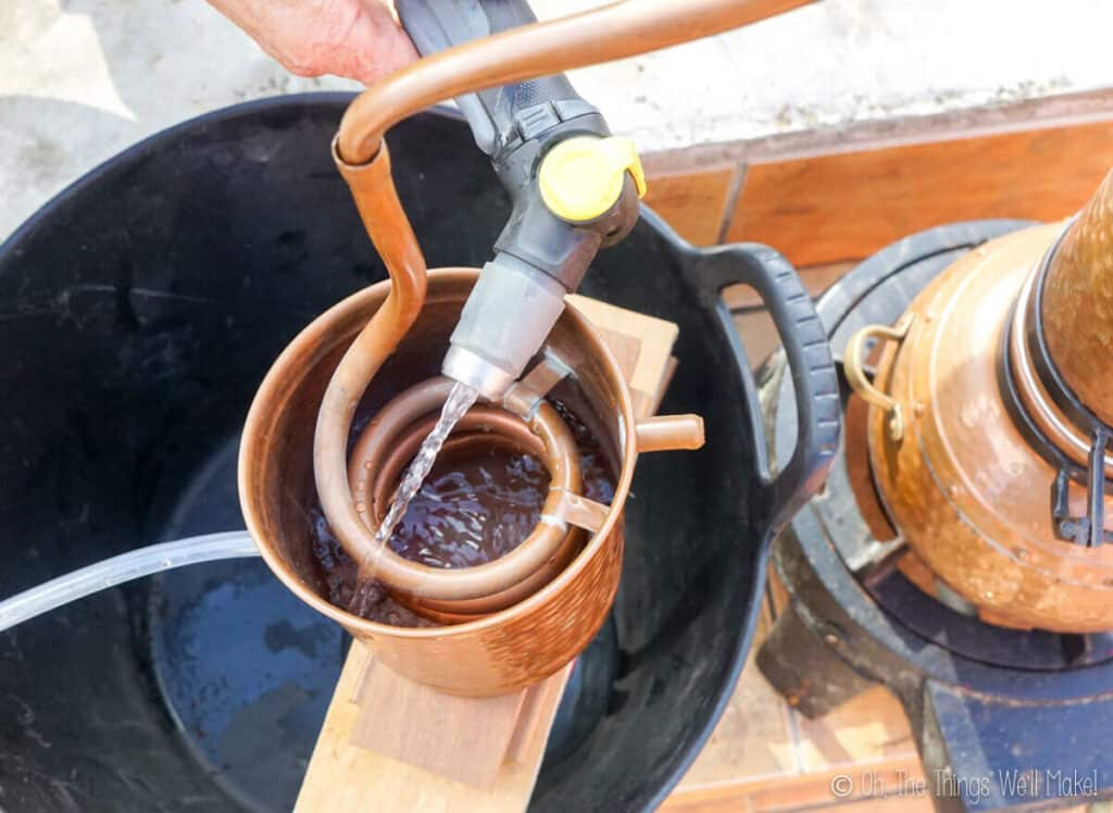 overhead view of water being sprayed over the copper coils of a still