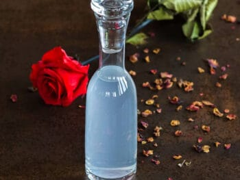 A bottle of homemade rose water hydrosol in front of a rose and rose petals