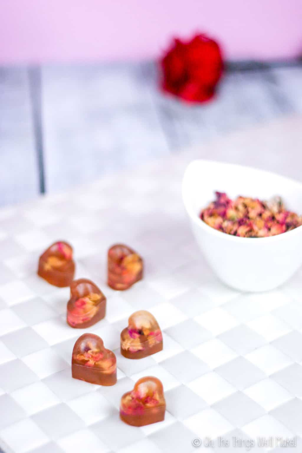 Close up of heart shaped gummy treats with real rose petals inside next to a bowl full of rose petals , placed on a white woven surface. A single red rose is at the background.