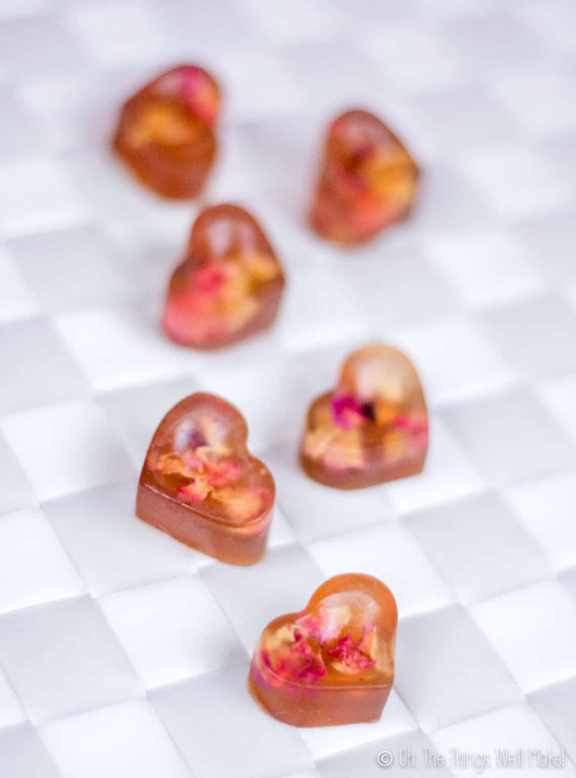 Close up of six heart shaped rose petal gummies on a white woven surface.