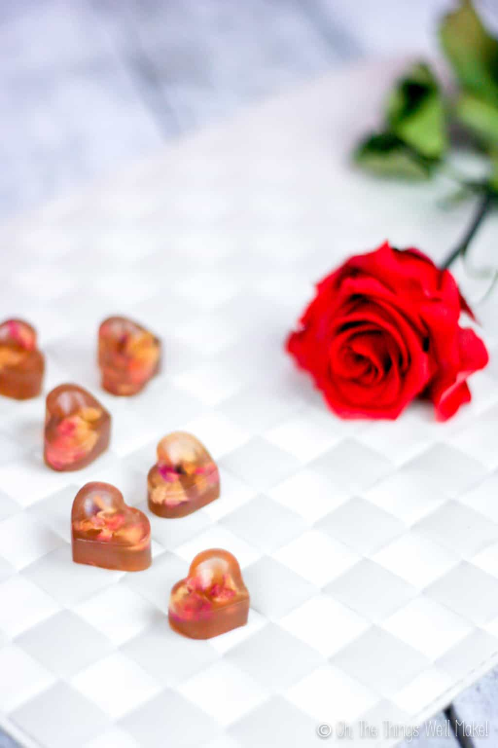 Close up of heart shaped gummy treats with real rose petals inside next to a red rose, placed on a white woven surface.