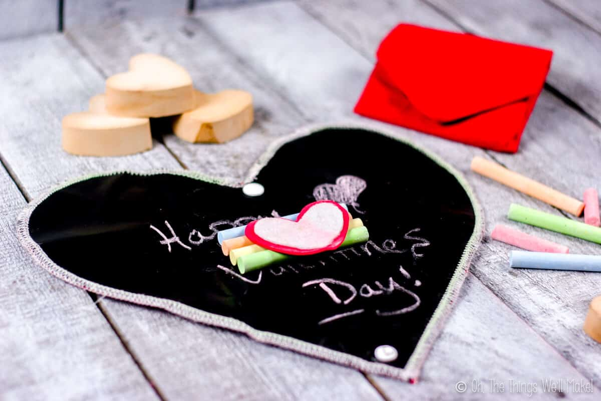 Heart chalkboard with four pieces of colorful chalk and a heart shaped chalkboard eraser in the center, placed on a grey wood surface. Surrounding the chalkboard are heart shaped wood blocks, a closed heart chalkboard, and four pieces of colorful chalk.