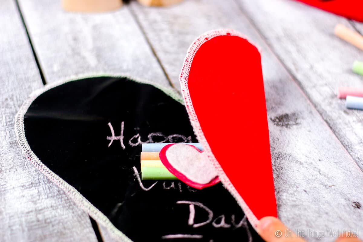 Chalkboard heart with the right side folded to the center over four pieces of chalk and heart shaped eraser.