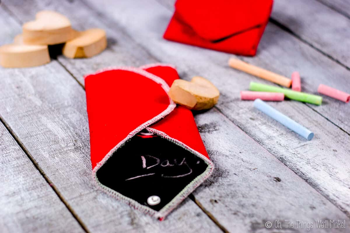 Close up of a folded heart chalkboard on a grey wood surface, surrounded with heart shaped wood blocks, a closed heart chalkboard, and four pieces of colorful chalk.