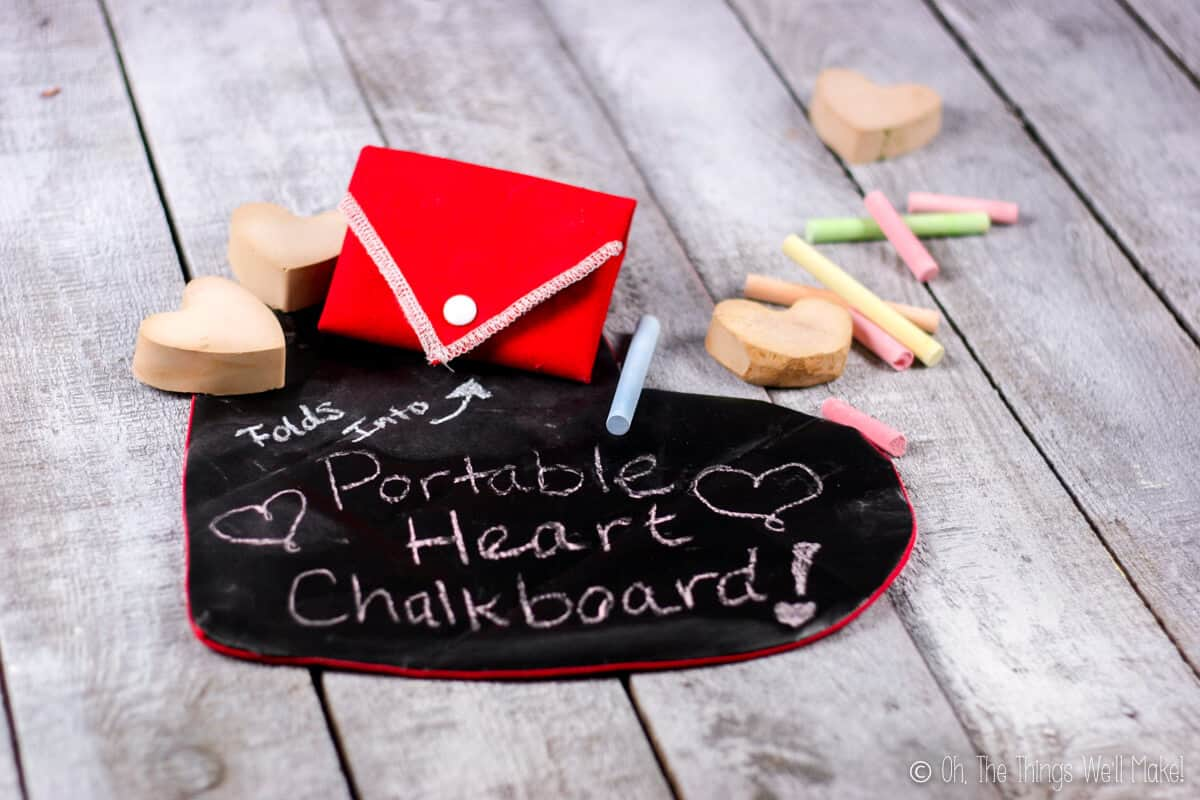 """Two foldable chalkboard hearts placed on a wood grey surface. One folded shut placed on top of an open one that has """"Portable Hearts Chalkboard"""" written on it."""