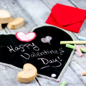 "A homemade cloth chalkboard heart with ""Happy Valentine's Day!"" written on it. It's surrounded by homemade chalk and next to a folded chalkboard."