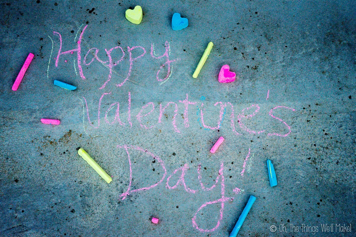 """Overhead view of """"happy Valentine's Day"""" written with homemade pink and blue chalk, with several pieces of heart shaped chalk and sidewalk chalk sticks laid around on the ground."""