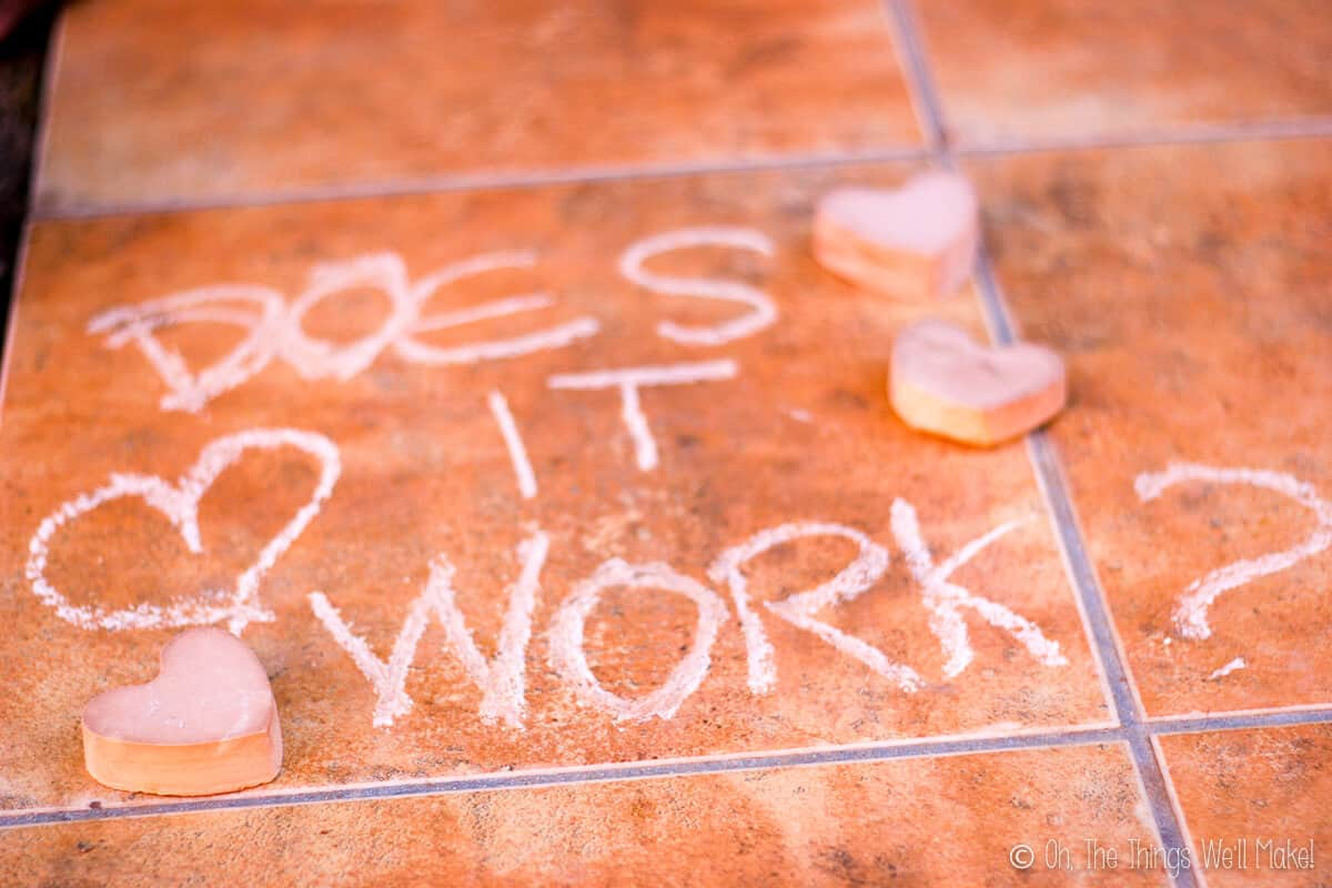"""""""Does it work"""" written on a brown tile with some pieces of heart shaped chalk laid around the writing."""