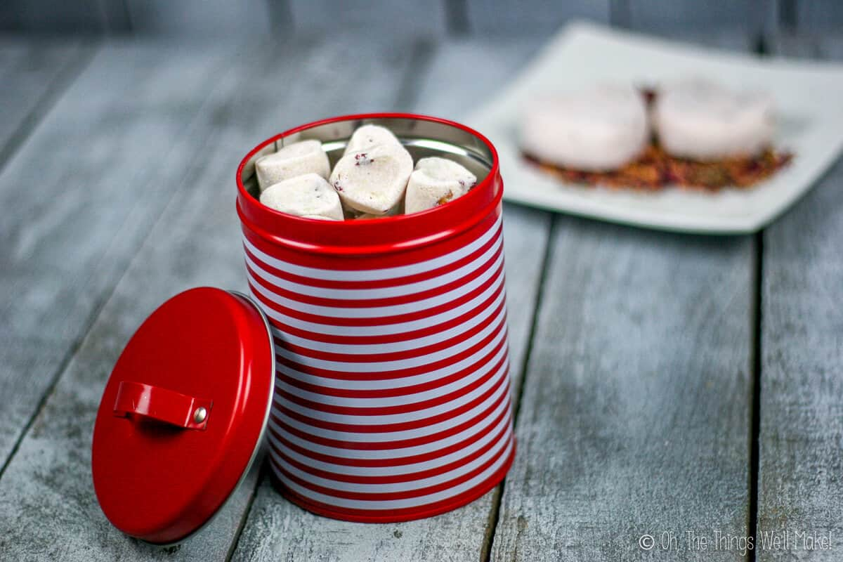 A red and white striped tin can filled with small rose petal bath bombs. Behind it, are two large bath bombs on a plate with rose petals.