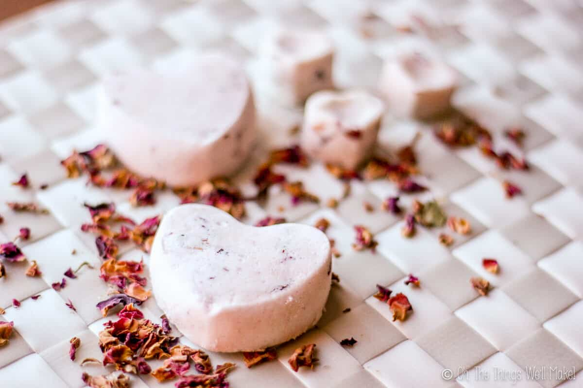 Several homemade rose petal bath bombs on a white woven placemat with some rose petals scattered on it too.