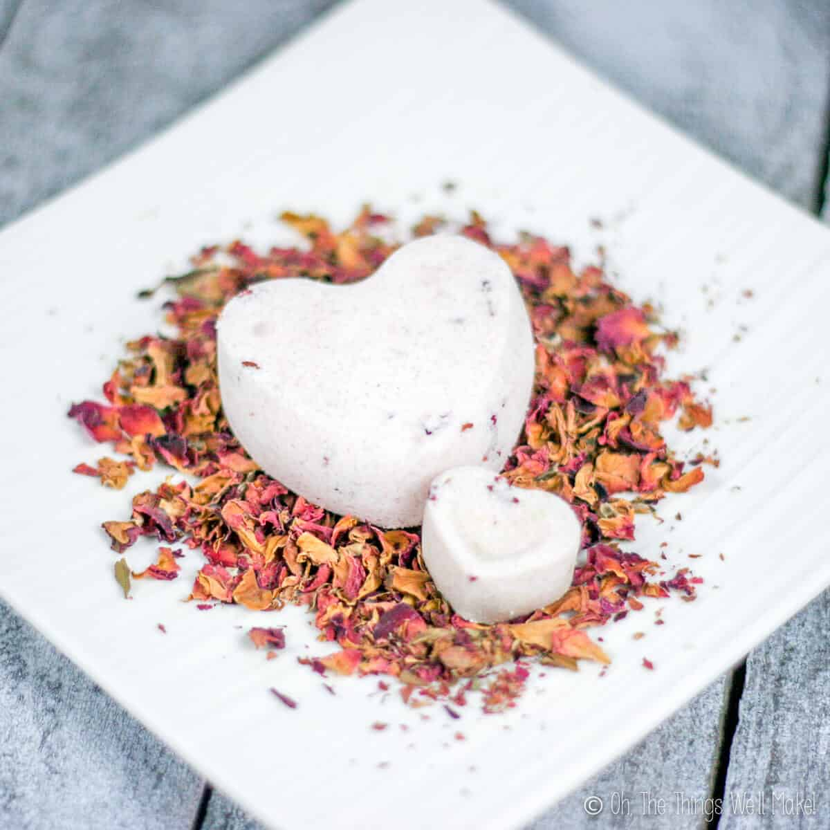 Close up of two heart shaped bath bombs. A large one and a small one placed on a plate full of rose petals.