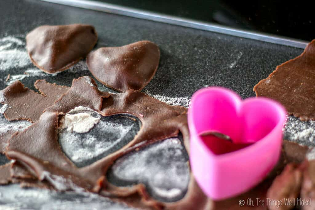 cutting out chocolate pasta with a heart-shaped cookie cutter.