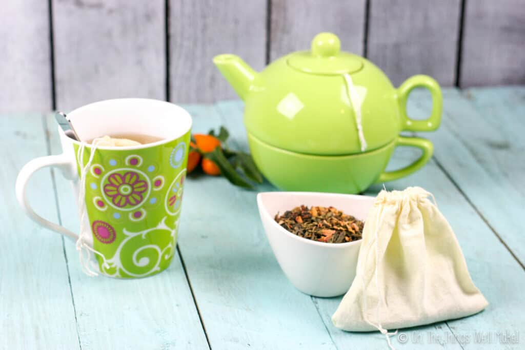 A cloth teabag in front of a small bowl with loose tea in it. In the background, there is a cup of tea and a teapot.