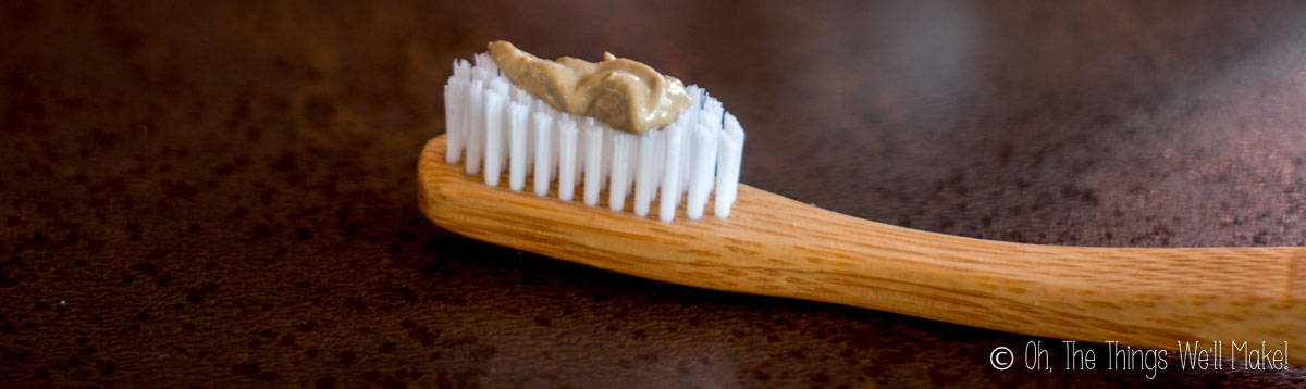 closeup of a homemade clay-based toothpaste on a bamboo toothbrush