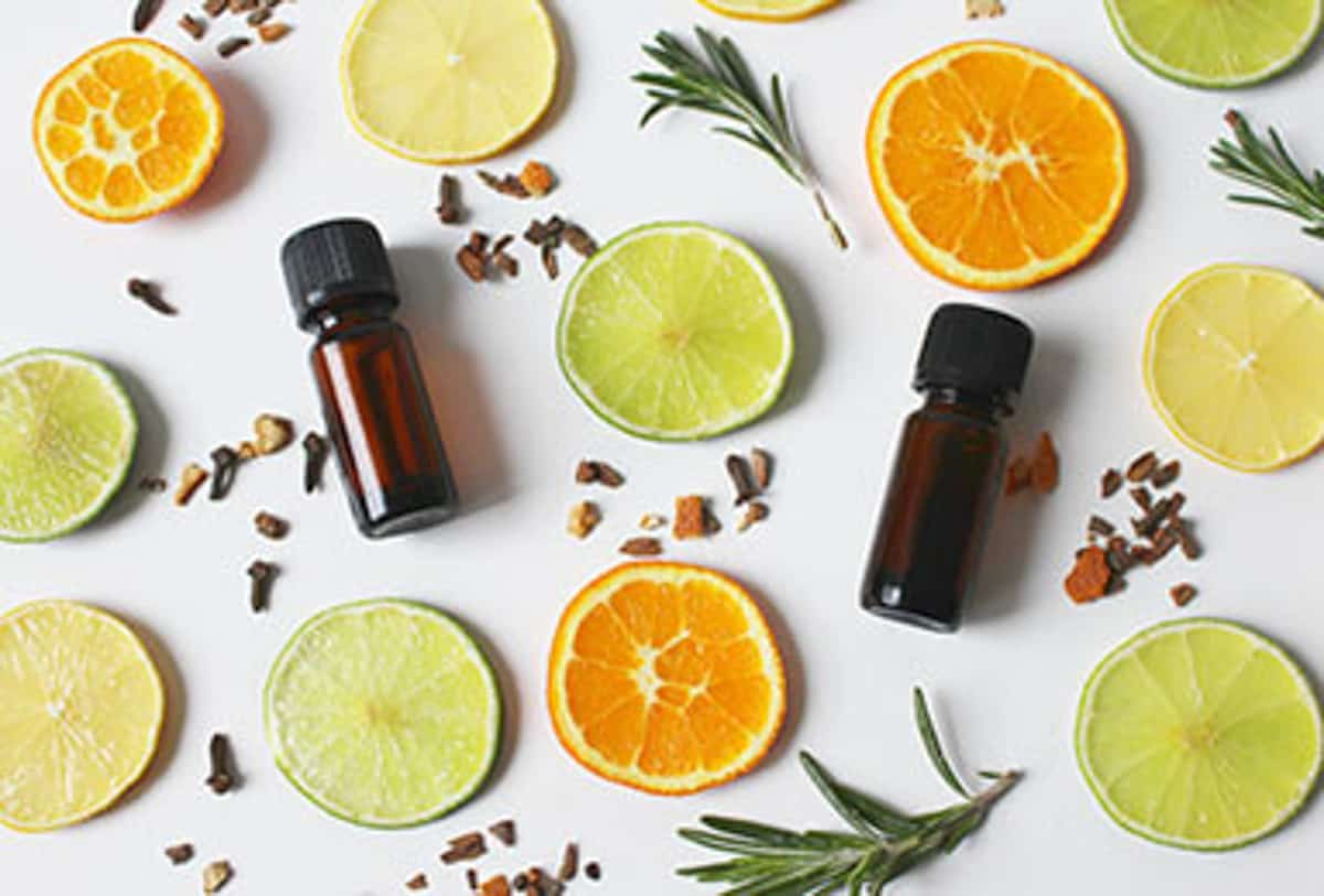 Overhead view of 2 ambar essential oil bottles surrounded by herbs, cloves, and slices of lemons and oranges
