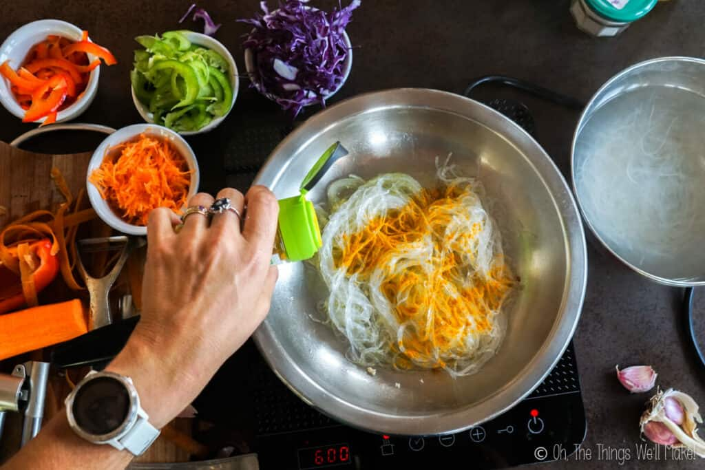 Overhead view of bean vermicelli in a stainless steel pan with turmeric sprinkled on top.