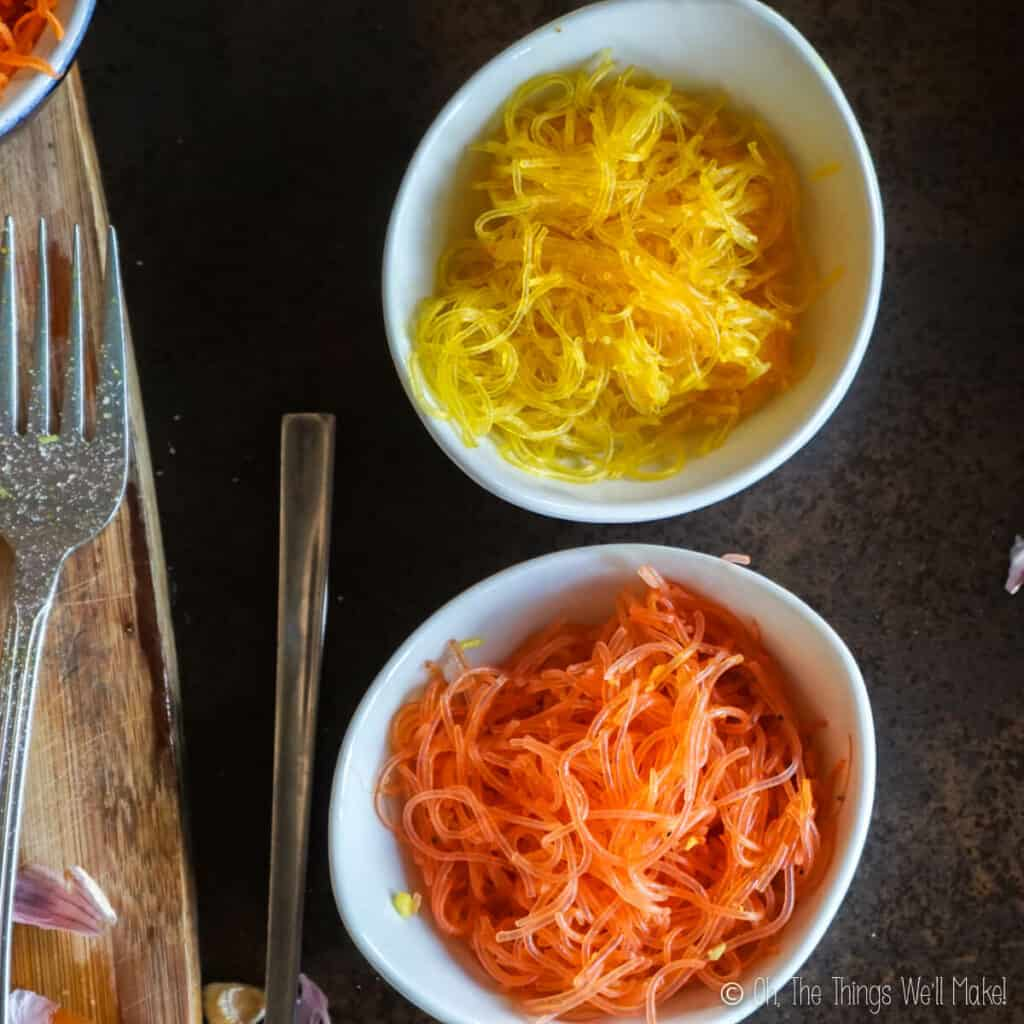 Overhead view of 2 bowls of bean vermicelli seasoned with turmeric: one is yellow and the other is orange.