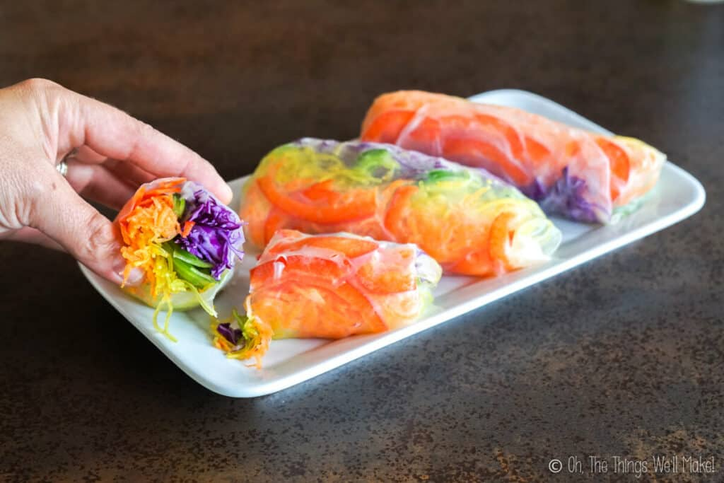 A closeup of a rainbow spring roll that has been cut in half to show the filling inside. In the background, 3 rainbow spring rolls are on a plate.