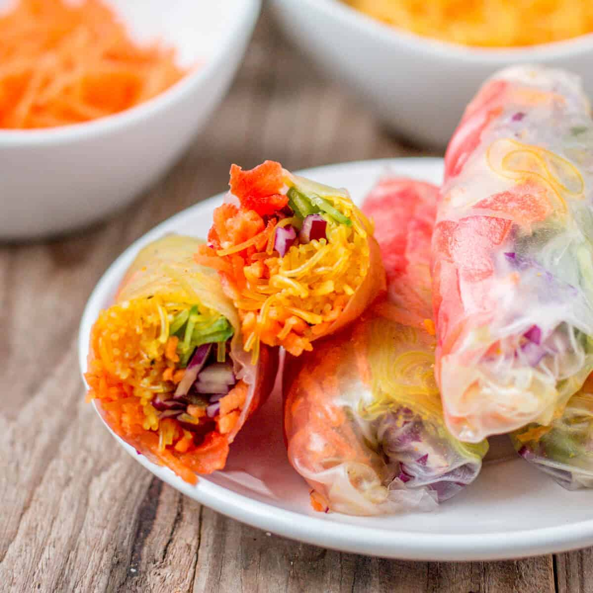 Closeup of a spring roll that has beeb cut in half on a plate showing the colorful rainbow of vegetables inside.