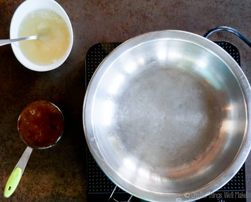 Overhead view of an empty pan with a cup of honey to the left, and a mixture of gelatin and water in a bowl above it.