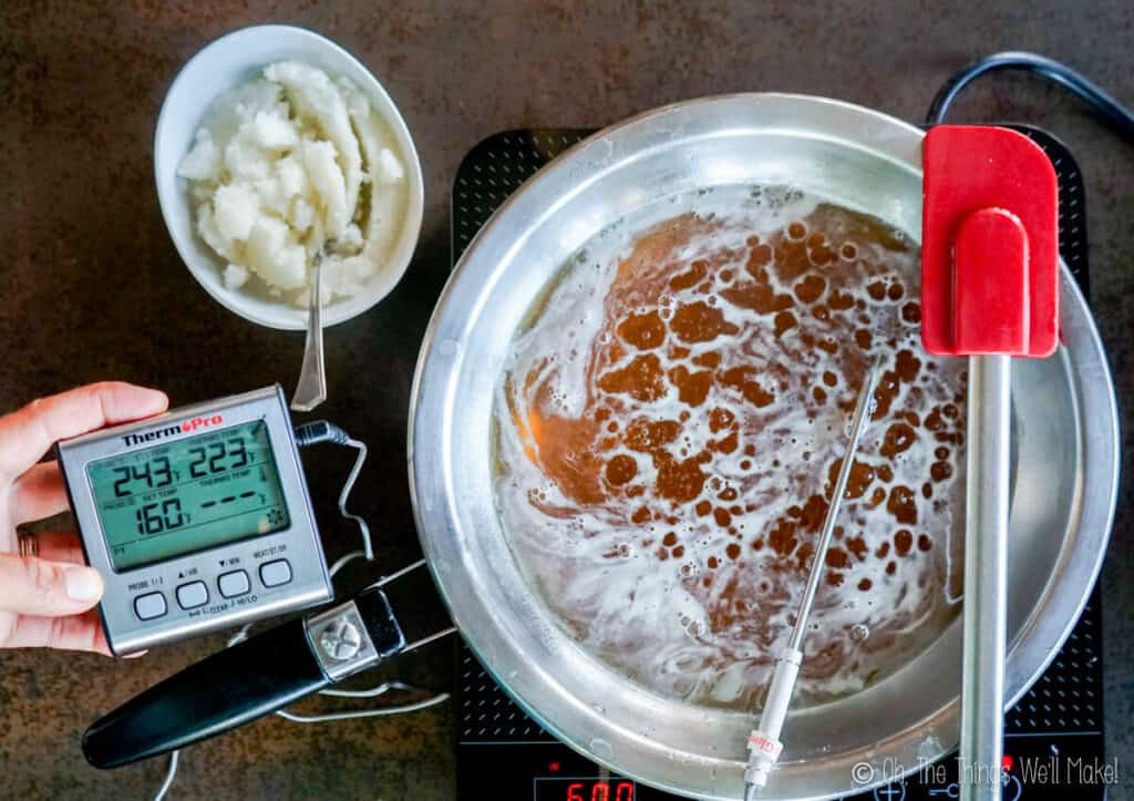 Overhead view of a honey mixture with a thermometer reading of 243ªF and a fully hydrated gelatin in a white bowl above it.