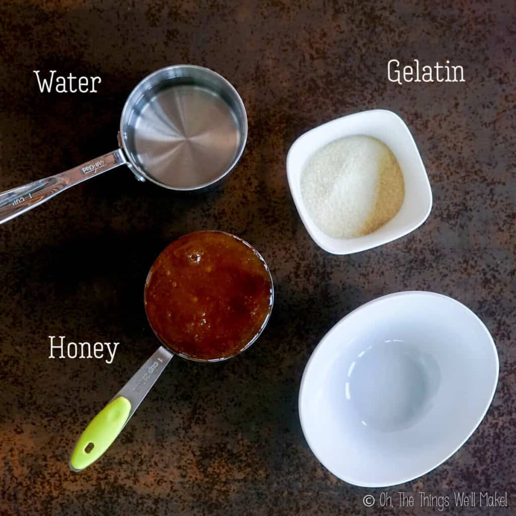 Overhead view of a cup of water, a cup of honey, some gelatin powder in a small bowl, and an empty bowl for mixing ingredients.