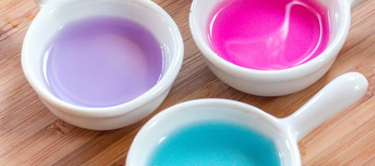 3 bowls of liquid, one turquoise, one pink, and one purple, in front of a bottle of liquid made from red cabbage, and next to a fresh red cabbage head sliced in half.