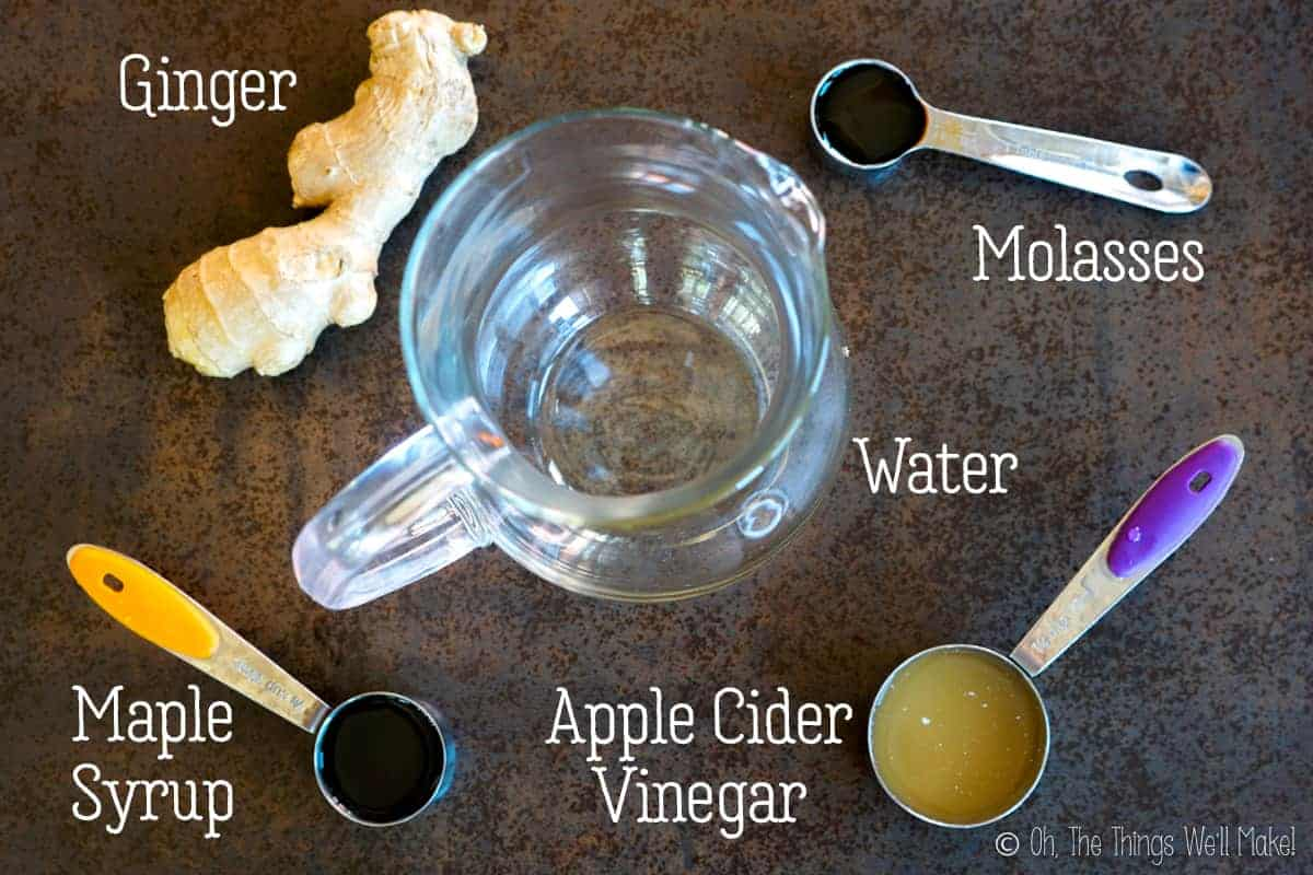 Overhead view of the ingredients for a ginger switchel, ginger, molasses, maple syrup, and applecider vinegar around an empty glass pitcher.