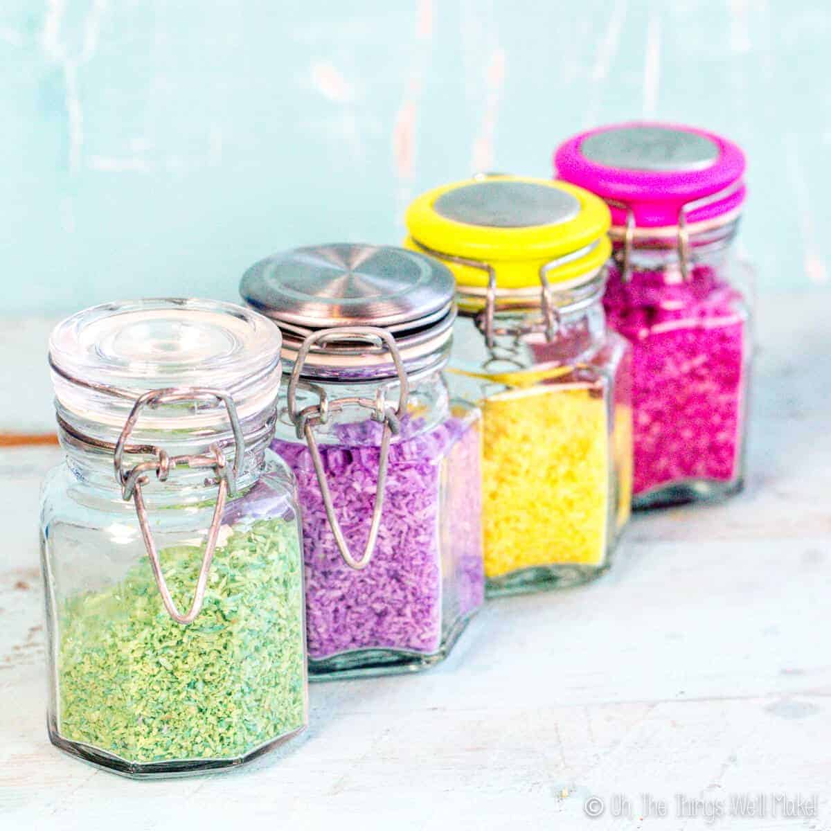 4 glass jars filled with 4 different types of colorful sprinkles made from shredded coconut. From left to right: green, purple, yellow, and bright pink.