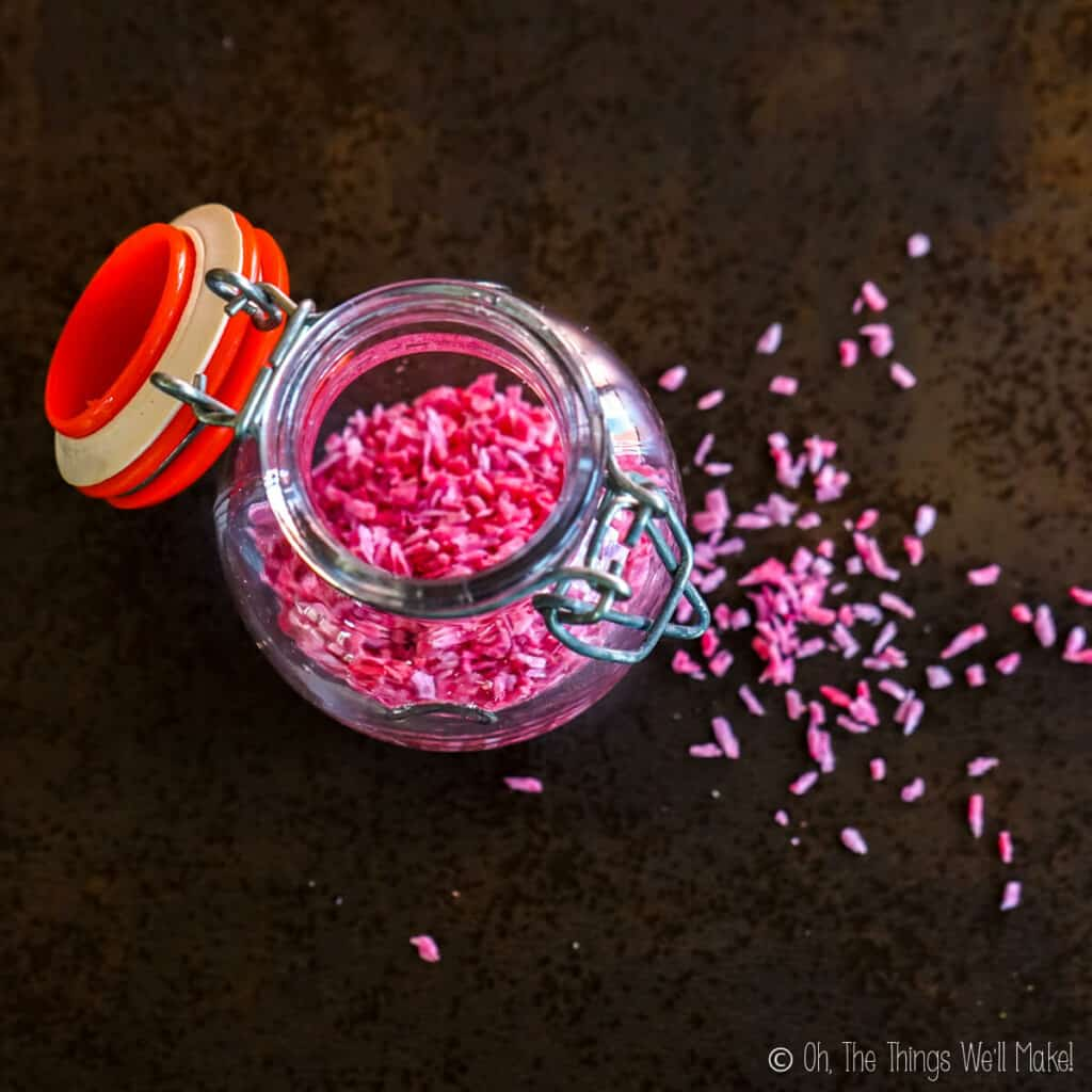 Overhead view of pink coconut sprinkles in an open jar, with sprinkles over the surface below it.