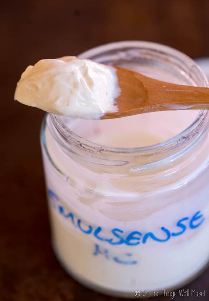 A spoonful of a lotion made with Emulsense HC emulsifier over a jar of it.