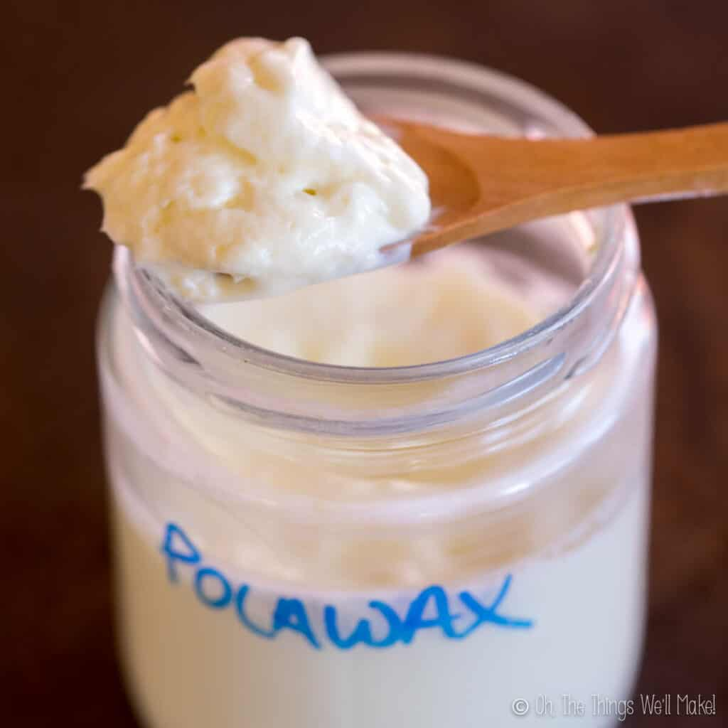 A jar of a thick lotion made with Polawax emulsifier. Some is on a spoon over the jar to better show the texture.