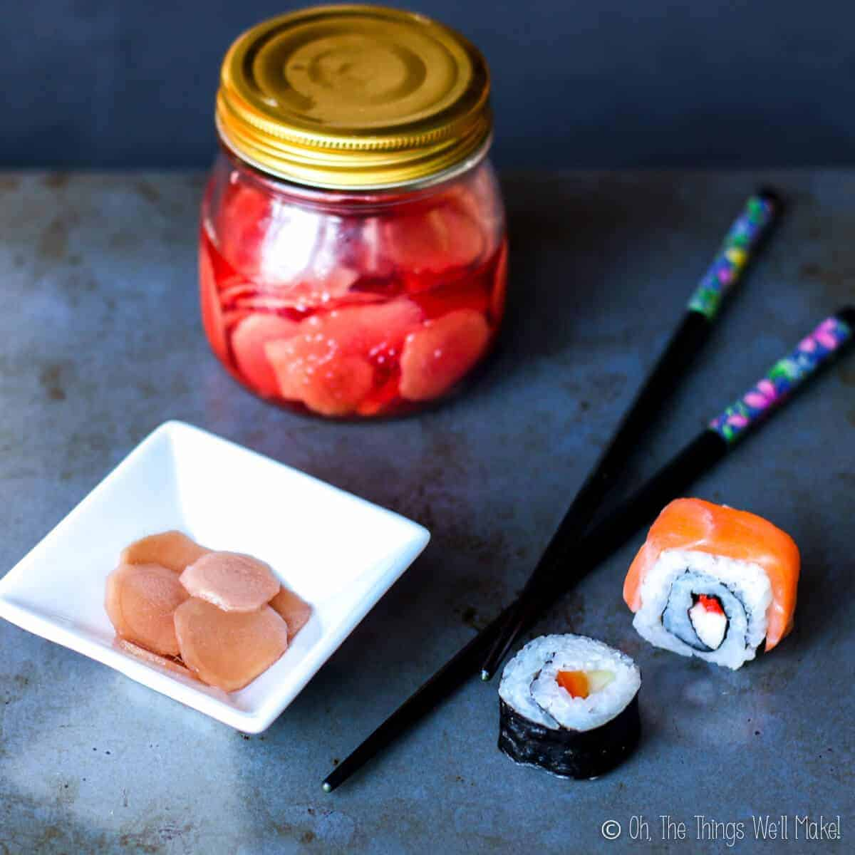 A jar of homemade pickled ginger for sushi next to some sushi and chopsticks