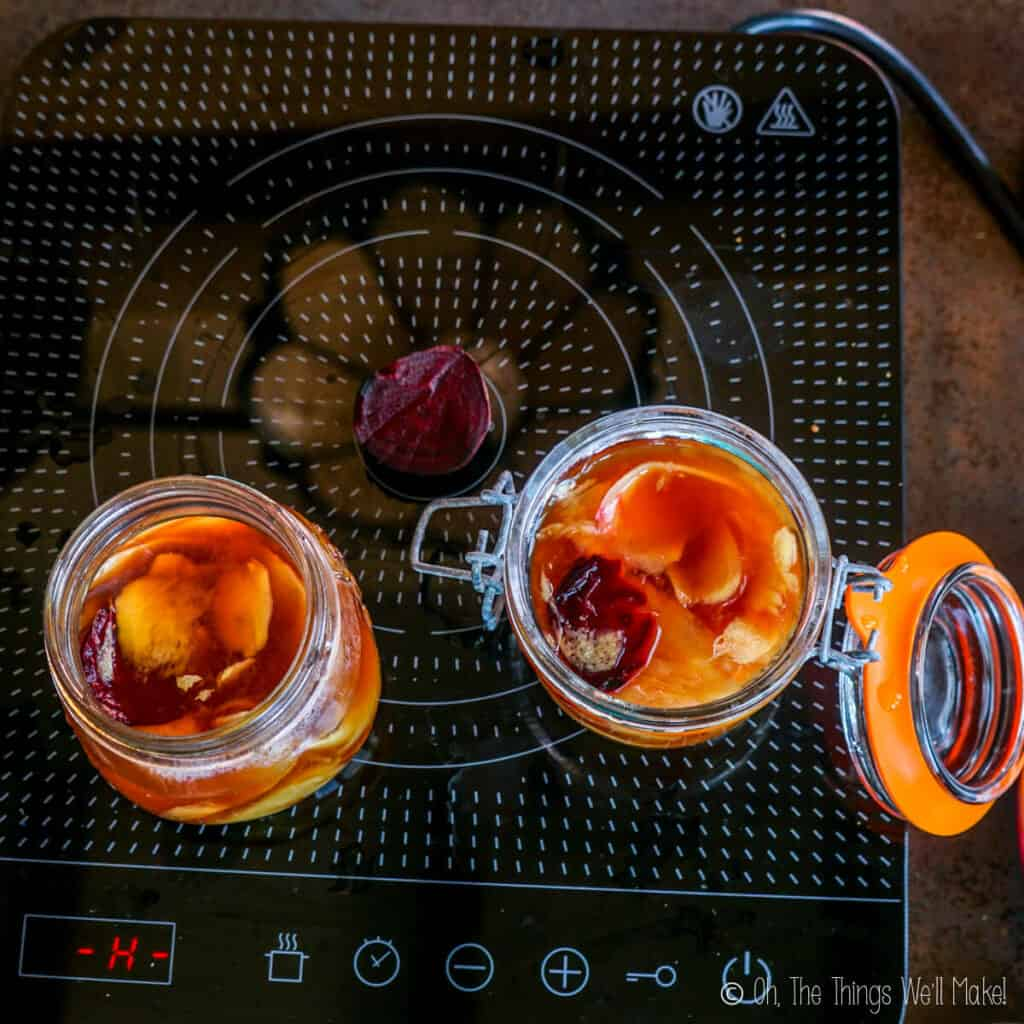 Adding slices of beets to 2 jars filled with ginger in a vinegar mixture.