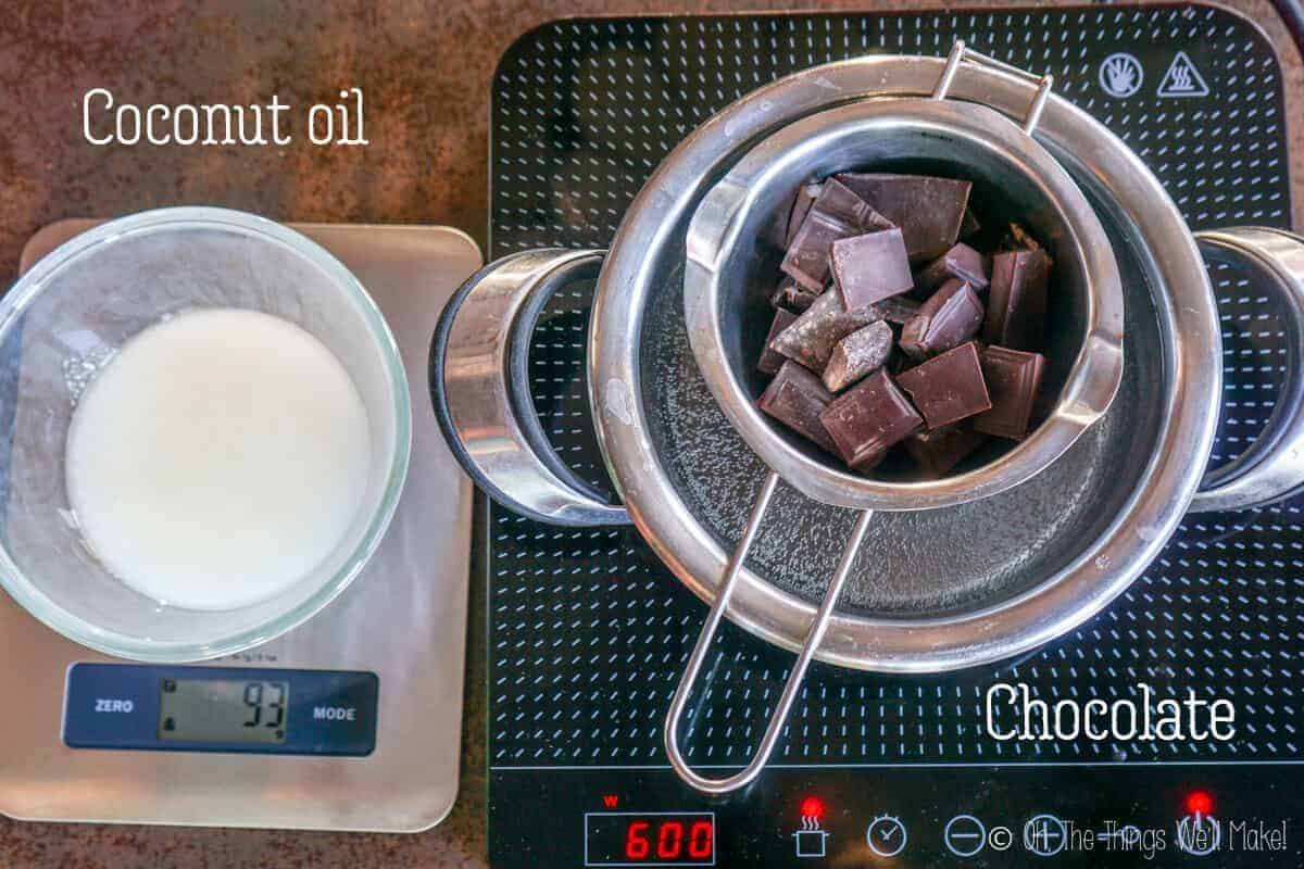 Top view of chopped chocolate inside a double broiler and a container of coconut oil on a measuring scale the left side.