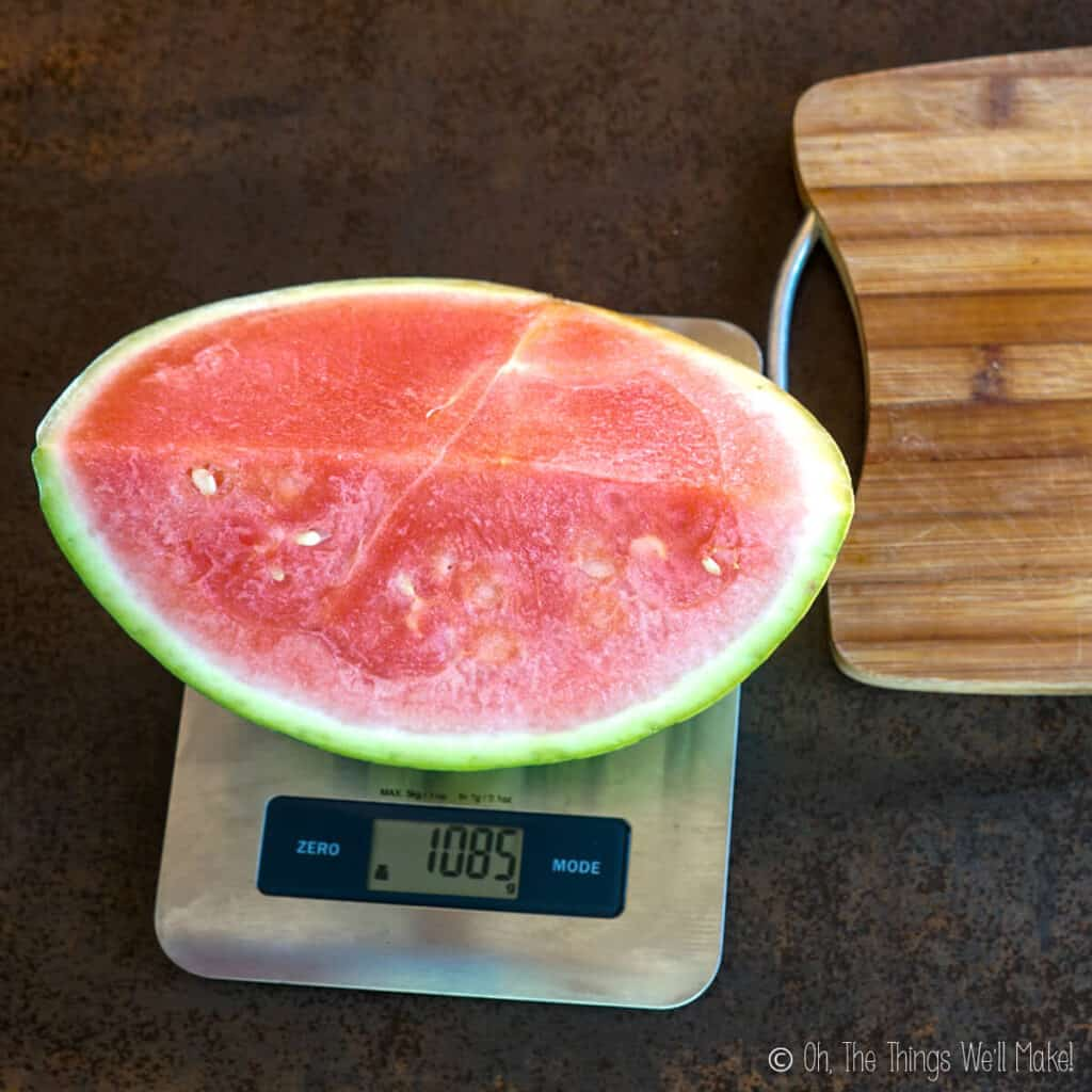 Overhead view of a quarter of a watermelon on a kitchen scale. It measures 1085 grams.