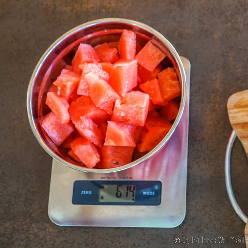 Overhead view of cubed watermelon in a bowl on a kitchen scale. It measures 614g.