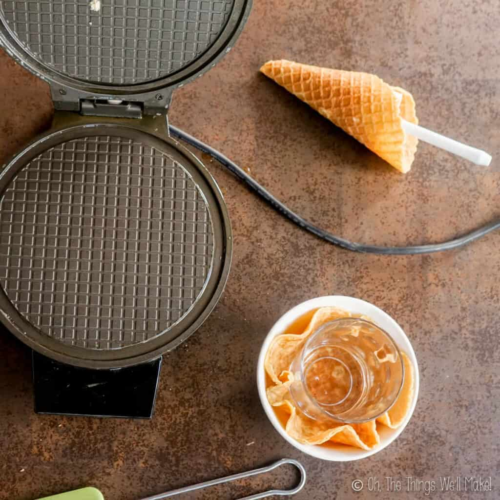 Overhead view of an open waffle cone iron, next to a homemade waffle cone and waffle bowl