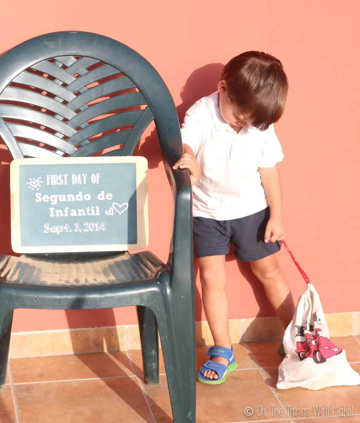 Upset young boy with his head down next to a sign made to memorialize the first day of school