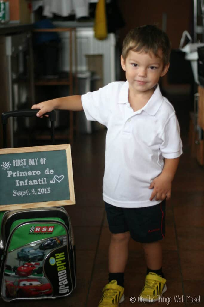 2 year old boy holding up a chalkboard sign on his first day of school.