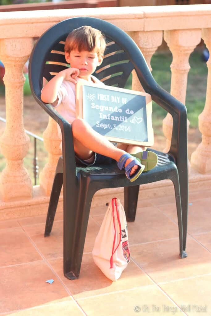 3 year old boy holding up a chalkboard sign on his first day of school.