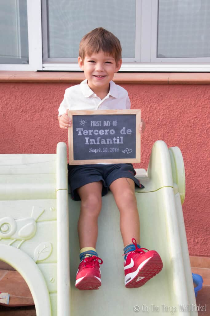 4 year old boy holding up a chalkboard sign on his first day of school.