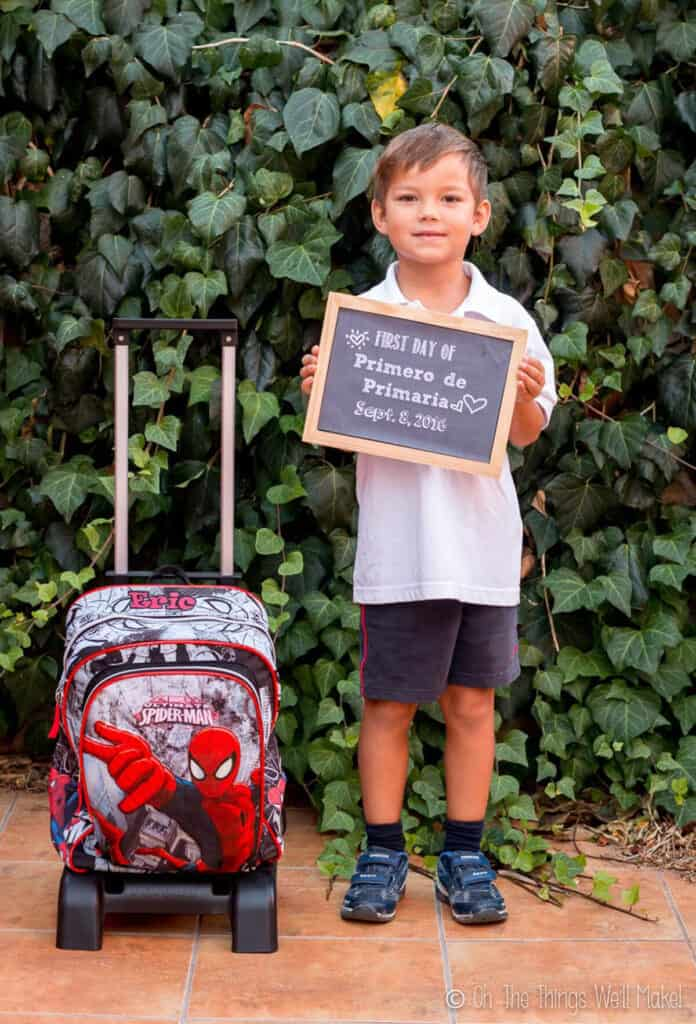 5 year old boy holding up a chalkboard sign on his first day of school.