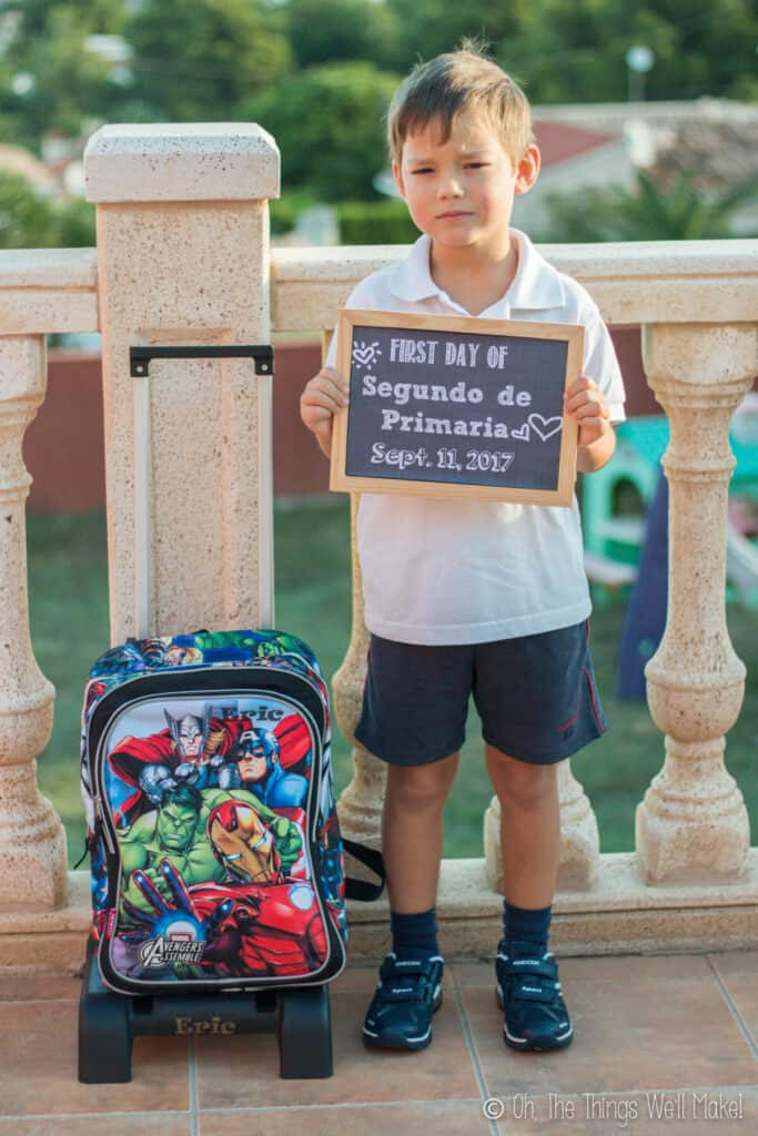 6 year old boy holding up a chalkboard sign on his first day of school.