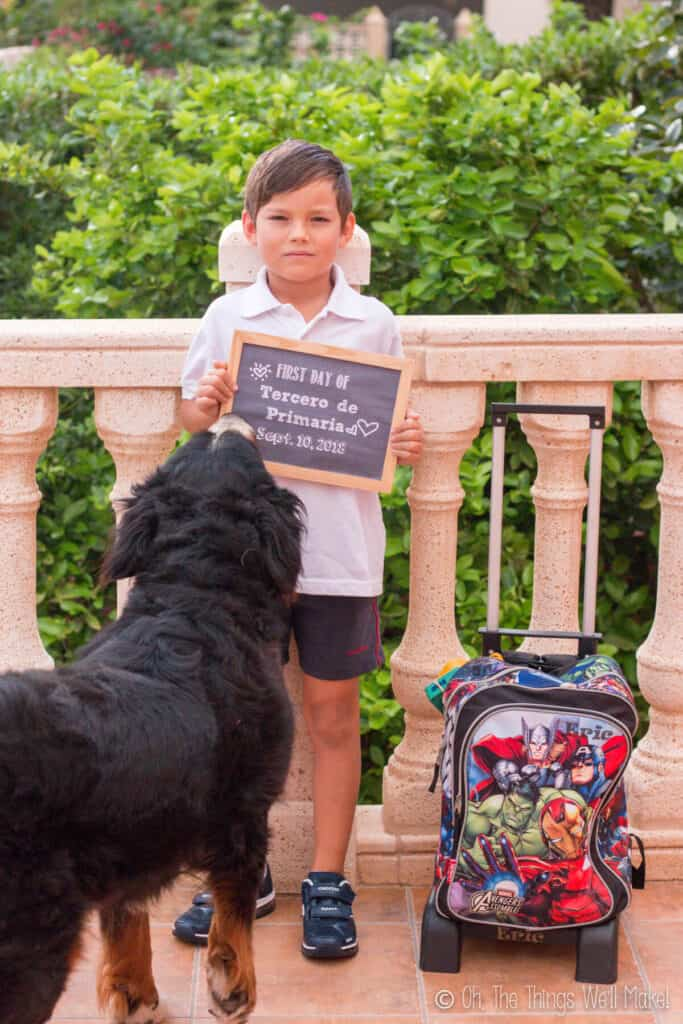 7 year old boy holding up a chalkboard sign on his first day of school.