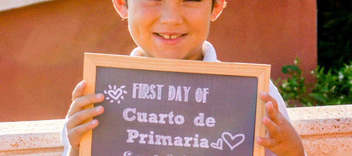 Closeup of boy holding a chalkboard siign on the first day of school