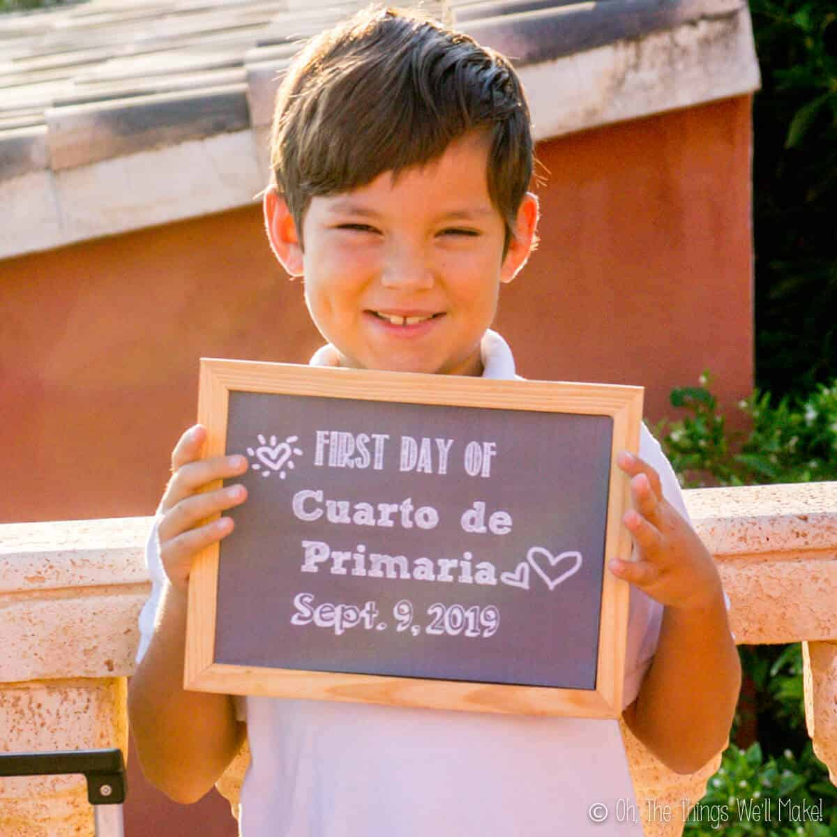 Closeup of boy holding a chalkboard sign on the first day of school