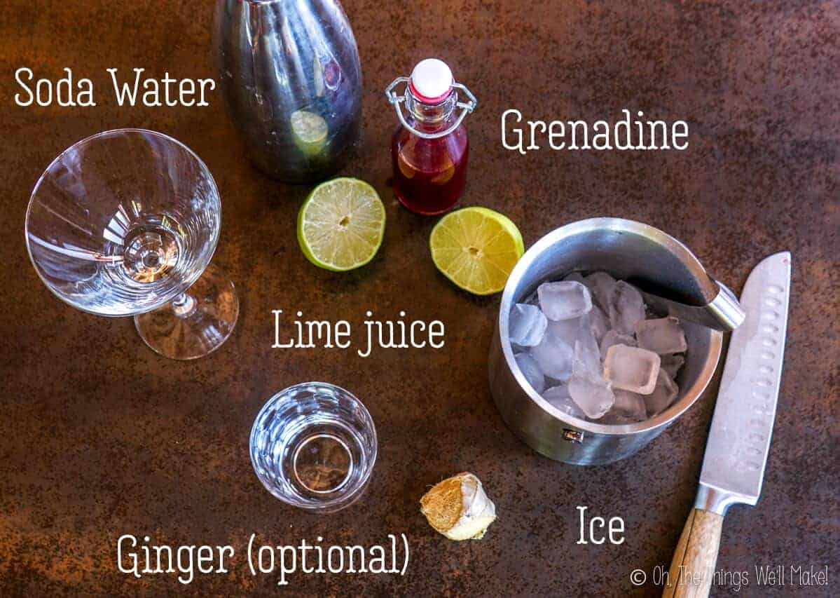 overhead view of the ingredients for a Shirley Temple Drink: lime, grenadine, ginger, ice, soda water