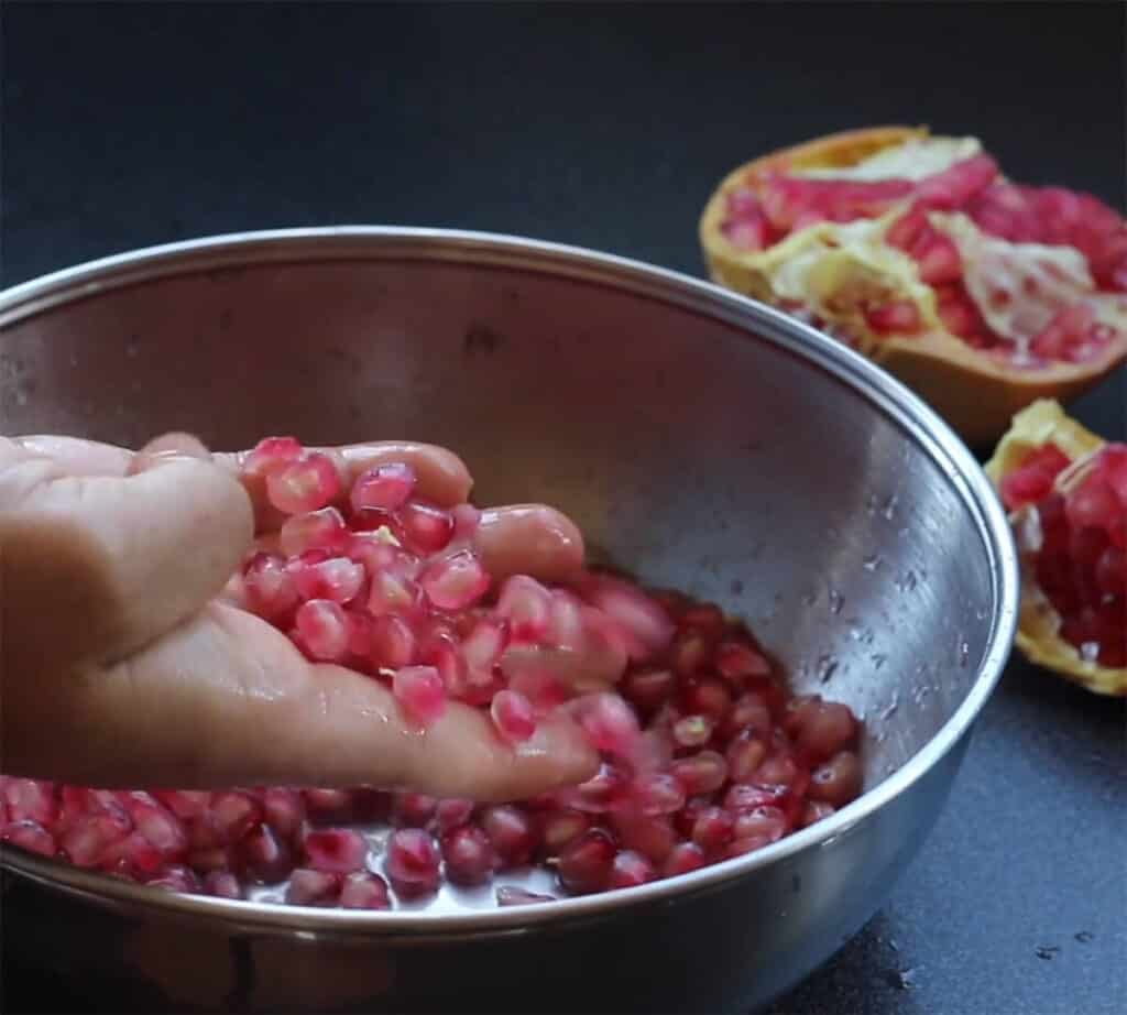 A hand picking up pomegranate seeds from a stainless steel bowl.
